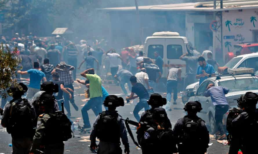 Palestinian worshippers run from teargas fired by Israeli forces