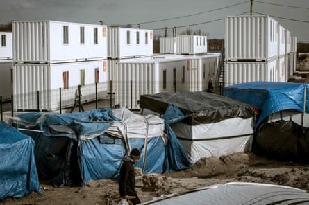The official shipping container shelters stand in stark contrast to the self-built shelters of the camp.