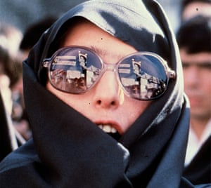 Revolutionary slogans and a portrait of Ayatollah Khomeini are reflected in the glasses of a demonstrator outside of the US Embassy in Tehran, November 1979.