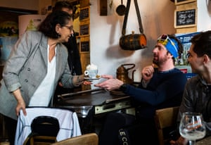 Joëlle, owner of D'Oude Hoeve handing a coffee to Bradley Wiggins