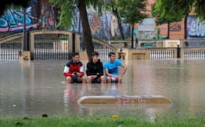 Boys sit on a bench in a park near the overflowing Segura river in Orihuela