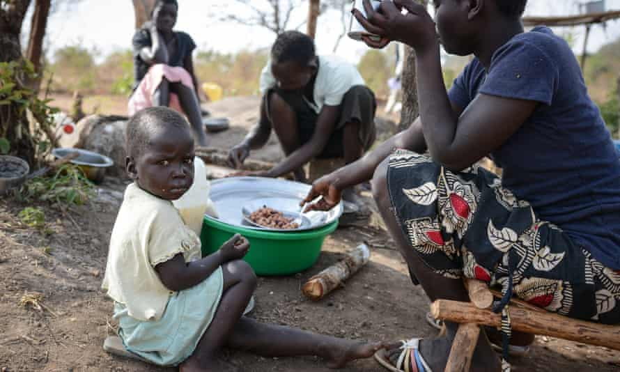 A South Sudanese family eat a meal in the Bidibidi camp in Ugand