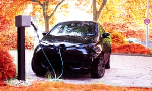 An electric car charging among trees