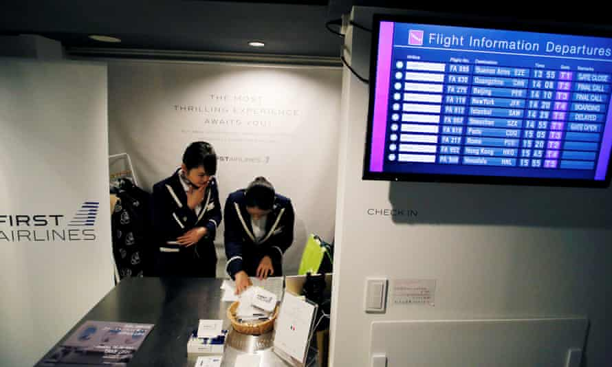 Staff dressed as flight attendants work at the First Airlines, virtual first-class airline check-in desk.