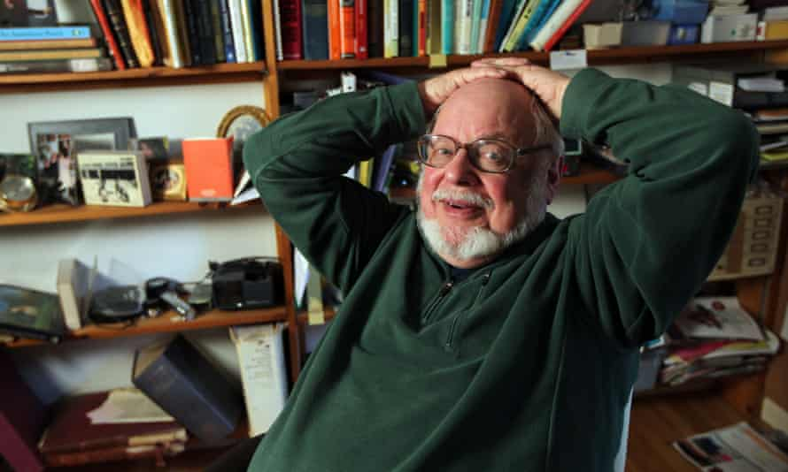 Norton Juster leaning back in his chair with his hands clasped on his head, in a green jumper, with shelves full of books behind