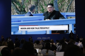A huge screen shows live video of North Korean leader Kim Jong Un and South Korean President Moon Jae-in talking privately