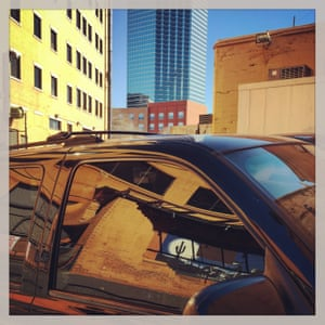 A car window reflects a wall mural on a building in downtown Dallas