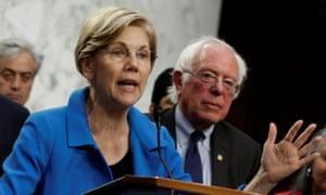 Senator Elizabeth Warren, with Bernie Sanders, speaks on Capitol Hill.