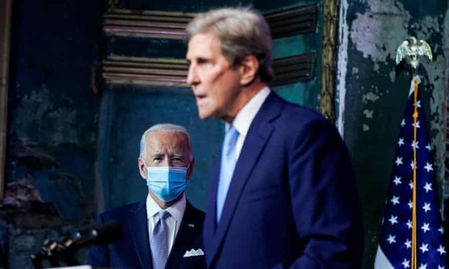 Joe Biden listens as John Kerry speaks