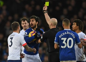 Referee Anthony Taylor shows a yellow card to Gomes.