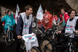 Cyclists wearing bibs that read 'Paris without cars' ride along the banks of the river Seine