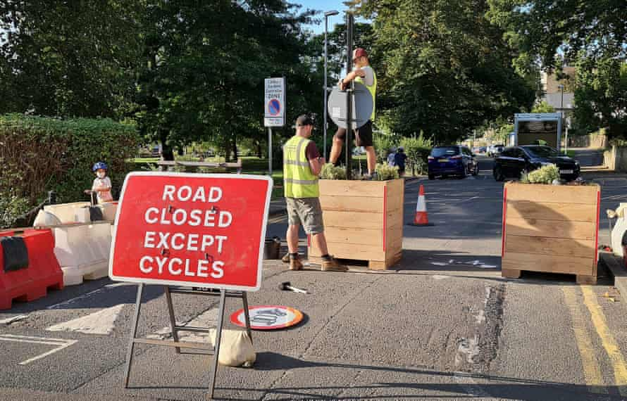 Workmen set up planters and signs for an LTN scheme in Kingston-Upon-Thames in London