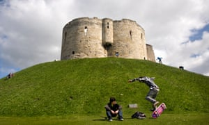 Skateboarders at the base of the mound of Clifford's Tower, York