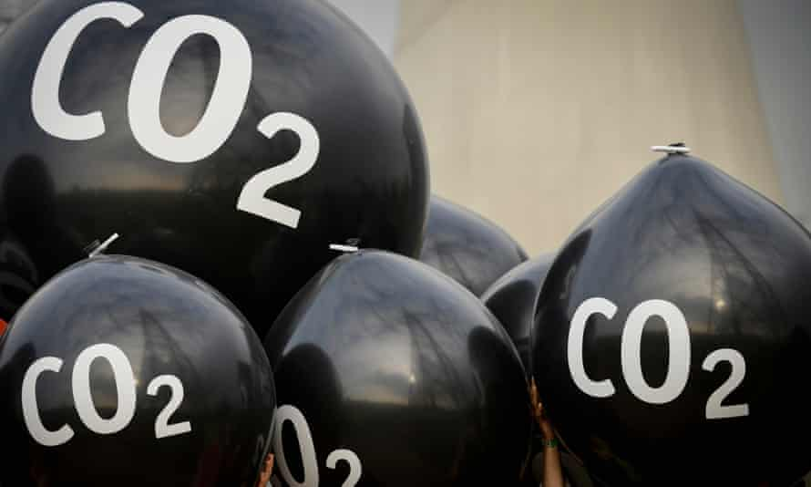 Activists hold giant balloons labeled 'CO2' in front of the Neurath coal power plant ahead of the Bonn climate summit