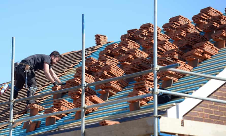 a roofer fits roof tiles