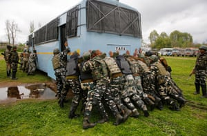 Indian paramilitary soldiers push their bus out of the mud at a polling equipment distribution centre. Elections for the Srinagar constituency are scheduled for this week