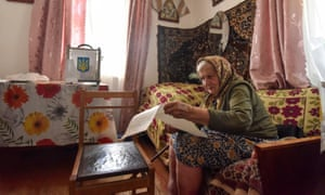 A resident studies her ballot at home during a parliamentary election in Lviv, Ukraine