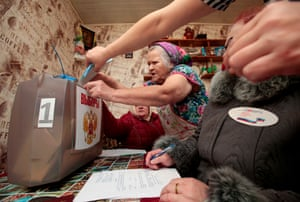 A woman casts her vote into a mobile ballot box in a settlement in the Smolensk region of west Russia