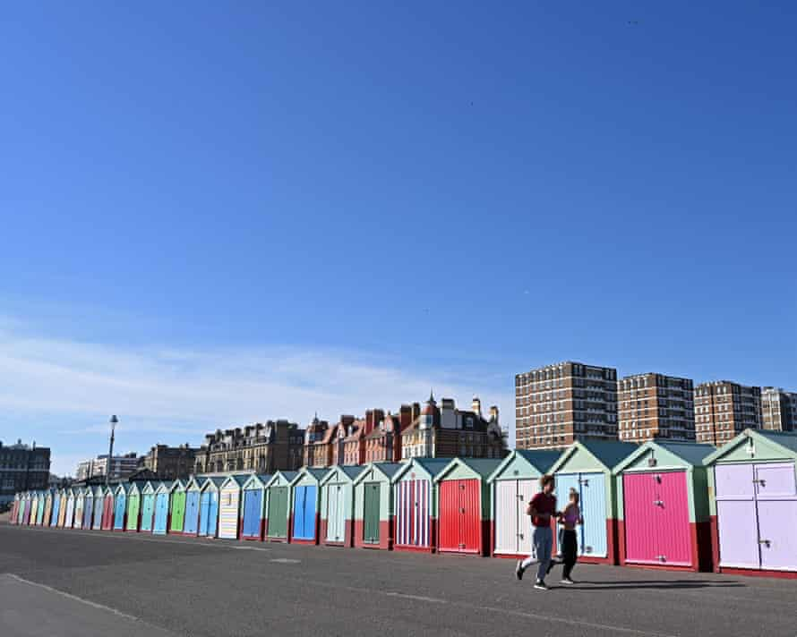 Joggers run past beach huts on the front in Hove last weekend.