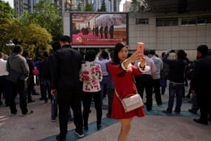 A woman takes pictures of herself in front of a TV screen shows a live news broadcast of Chinese President Xi Jinping introducing his Politburo Standing Committee