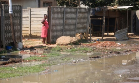 A resident watches raw sewage flow just outside her house in Glen View.