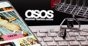 A smartphone with the ASOS app and a keyboard and shopping cart are seen in front of a displayed ASOS logo in this illustration picture taken October 13, 2020. REUTERS/Dado Ruvic/Illustration/File Photo