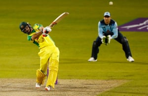 Maxwell hits a six to reach a century.