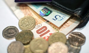 Pound coins and UK banknotes from a wallet.