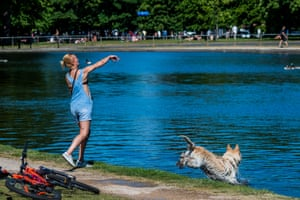 Woman exercises dog by lake