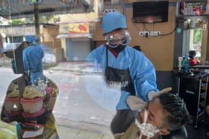 Siliguri, India: a salon worker cuts a customer's hair after the government eased a nationwide coronavirus lockdown