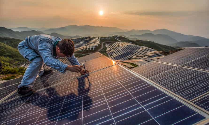 A worker at Xinyi photovoltaic power station in Songxi, China. China will lead the world for growth in renewable power, the IEA has predicted.