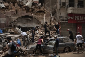People remove debris from a house damaged by the explosion in Beirut.