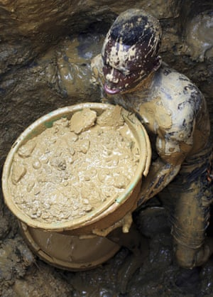 Miner with bucket of mud at a gold mine in DRC