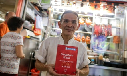 Chan Hong Meng, the owner of Hong Kong Soya Sauce Chicken Rice and Noodle, poses with his Michelin Award in front of his store in Singapore.