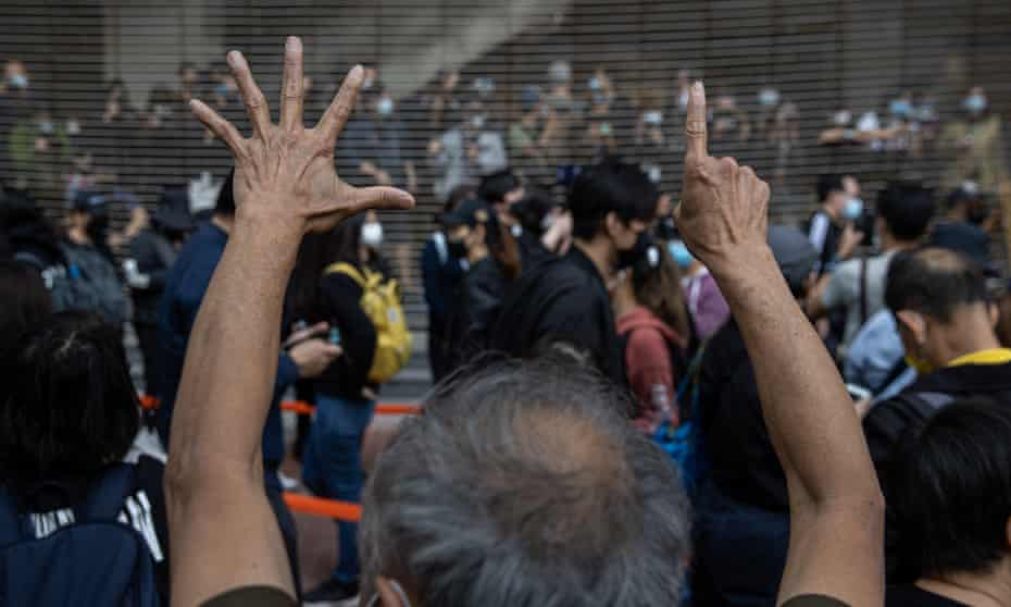 Pro-democracy activists gesture 'five demands, not one less' in support of arrested fellow activists outside the West Kowloon Court in Hong Kong