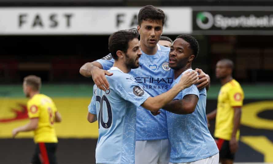 Raheem Sterling celebrates scoring Manchester City's first goal at Watford with teammates Rodri and Bernardo Silva.