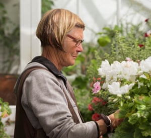 Jo Crispin tends her pelargoniums in the glasshouse at Offham House