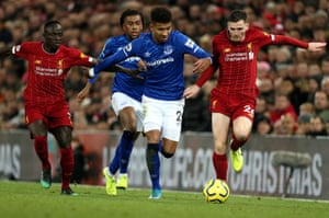 Everton's Mason Holgate (centre) and Liverpool's Andrew Robertson (right) tussle for the ball.
