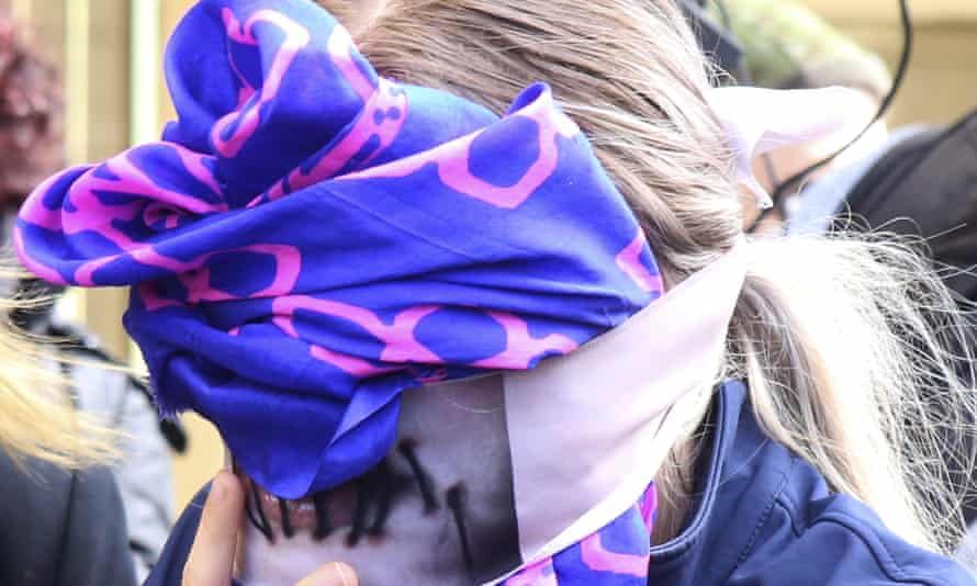 A 19-year old British woman covers her face as she leaves the Famagusta court after her trial, in Paralimni, Cyprus