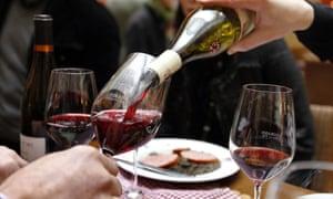 A waiter pours glasses of Beaujolais Nouveau wine at an event in Paris