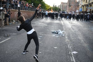 A woman throws a bottle towards the police