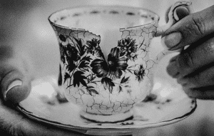 Close up of person's hands holding cup and saucer