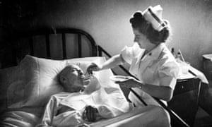 A nurse feeding an elderly patient, 1948.