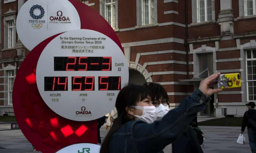 Two women take a selfie with a Tokyo 2020 countdown clock displaying the current date and time outside Tokyo Station. The coronavirus pandemic has forced the postponement of the Games.