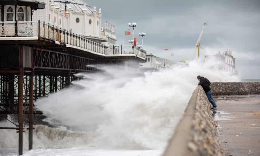 A man watches waves breaking near Brighton Pier