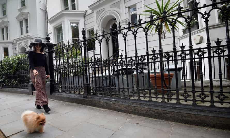 A woman walks her dog along a residential road in Kensington in London,