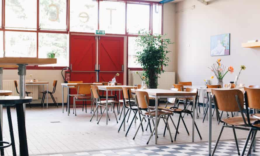 A dining area at De School club in Amsterdam. The daytime image shows desks and chairs used as places to dine in a large, communal room.