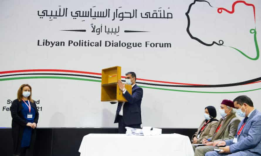A staff member shows the empty ballot box after delegates voted for a new interim Libyan government in Geneva