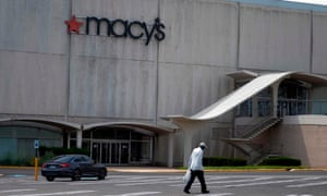 A man carries a bag through an empty parking lot in front of Macy's department store in Camp Springs, Maryland.