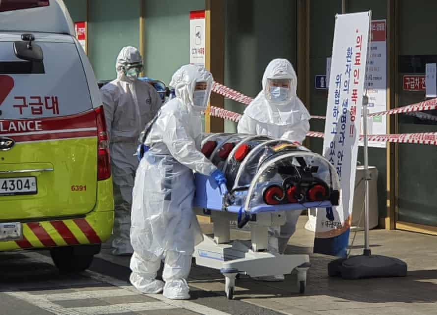 Medical staff move a patient suspected of contracting the coronavirus in Daegu.